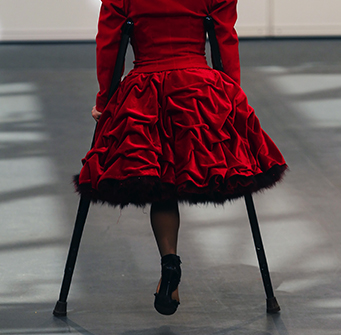Woman with one leg and crutches moves down a runway in a ruffled red dress.