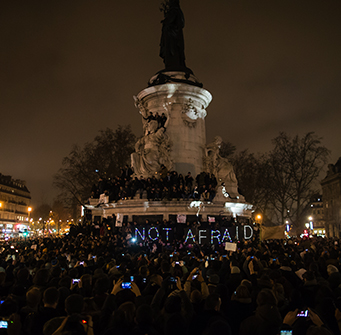 A large group of people gather in a city square with the words NOT AFRAID held up in lights.