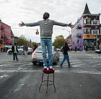 Man stands on a stool in the middle of the street with arms outstretched.