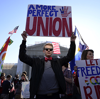A man in sunglasses and bowtie holds up a sign in a group of protestors which says A MORE PERFECT UNION.