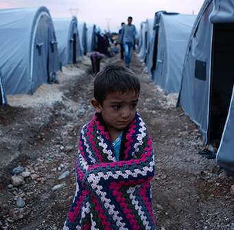 A boy stands alone in the middle of a camp wrapped in a blanket