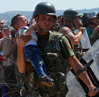 A soldier holds up a crying toddler in a sea of moving people
