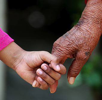 A young child and elderly person hold hands.