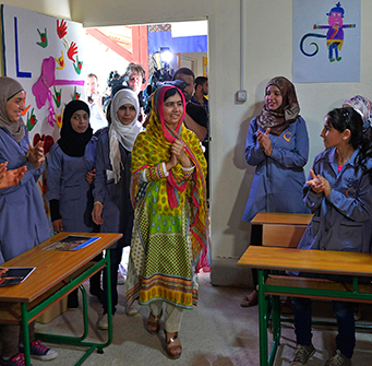 A woman walks into a classroom of muslim children with cameras following her.