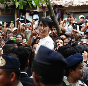 A woman stands up in a crowd of people holding cameras.