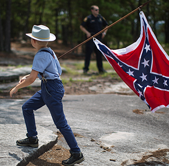 A boy crosses the street holding a Confederate flag.