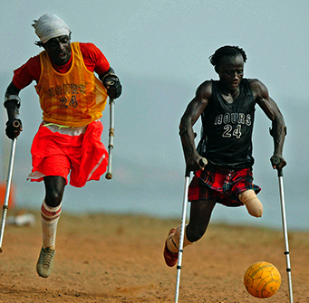 Two one-legged men with crutches play soccer.