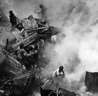 A group of people sift through a pile of rubble in black and white.