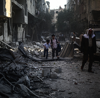 School children walk through war-torn streets.