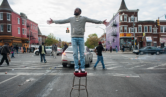 A man stands on a stool in the middle of the street with arms outstretched.