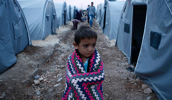 A boy stands alone in the middle of a camp, wrapped in a blanket.