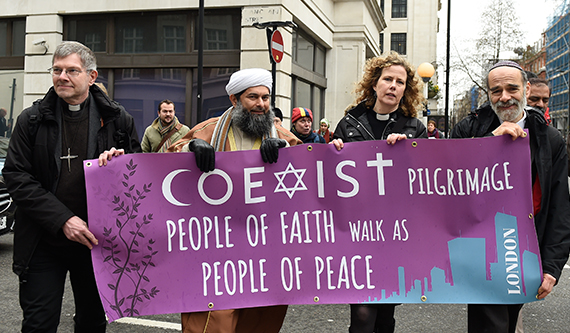A group of religious leaders from various faiths march with a COEXIST PILGRIMMAGE sign.