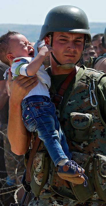 A soldier holds up a toddler in a sea of moving people.